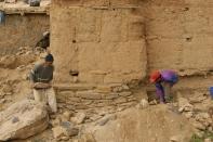 Local craftsmen repair a historic foundation.