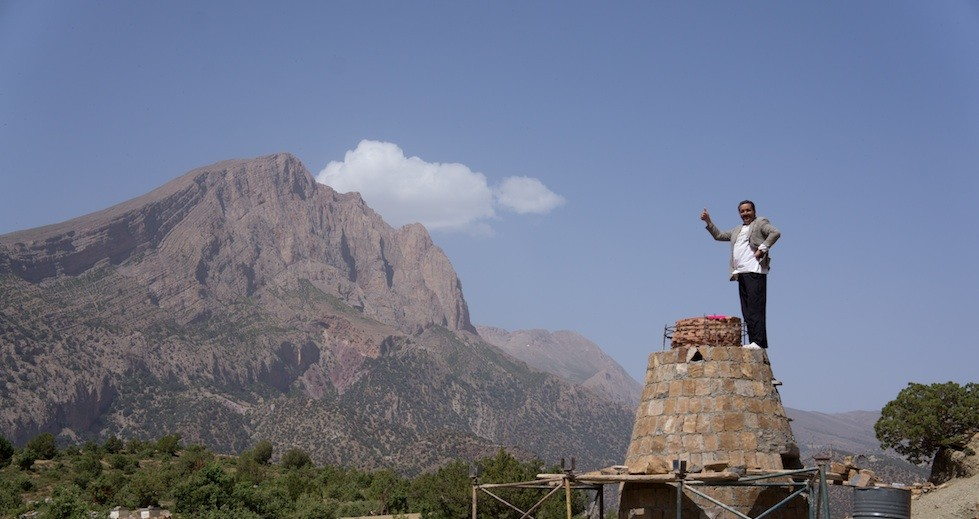 The sheikh of Zawiya Ahansal stands on top of the almost complete refuse oven.